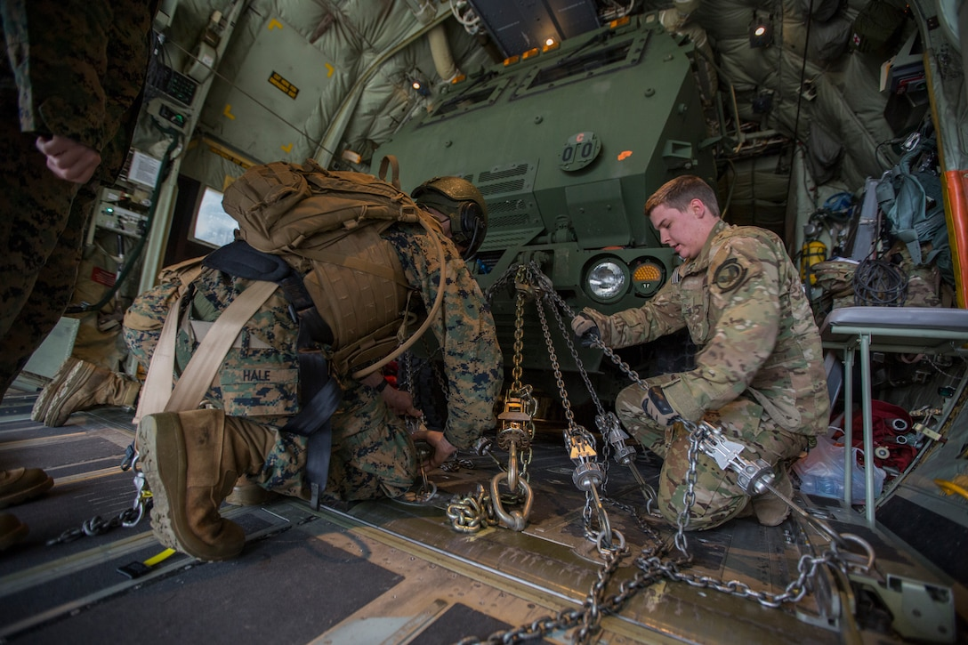 Air Force Senior Airman Brandon Lowe (right), a loadmaster with the 9th Special Operations Squadron, and Marine Corps Sgt. Jeffery Hale (left), a launcher chief with Kilo Battery, 2nd Battalion, 14th Marine Regiment, chain down a Marine Corps an M142 High Mobility Artillery Rocket System (HIMARS) onto an Air Force MC-130 at Fort Campbell, Ky., March 29, 2018. Marines from Kilo Battery flew from Fort Campbell to Dugway Proving Grounds, Utah, where they offloaded and fired four HIMARS missiles, demonstrating a unique capability that will give commanders more options to deal with threats when other options are not appropriate.