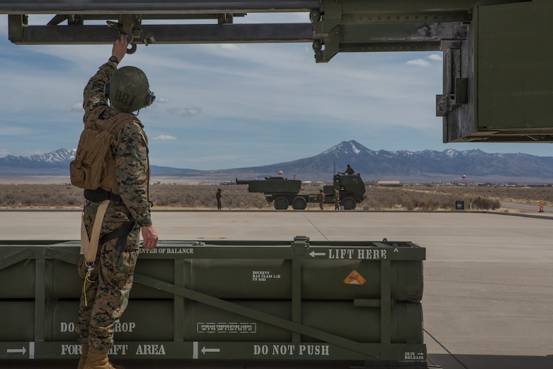 Marine Corps Sgt. Jeffery Hale, a launcher chief with Kilo Battery, 2nd Battalion, 14th Marine Regiment, guides a hoist up on an M142 High Mobility Artillery Rocket System (HIMARS) after dropping off a missile pod, at Dugway Proving Grounds, Utah, March 30, 2018. Marines from Kilo Battery flew from Fort Campbell, Ky., to Dugway where they offloaded and fired four HIMARS missiles, demonstrating a unique capability that will give commanders more options to deal with threats when other options are not appropriate.