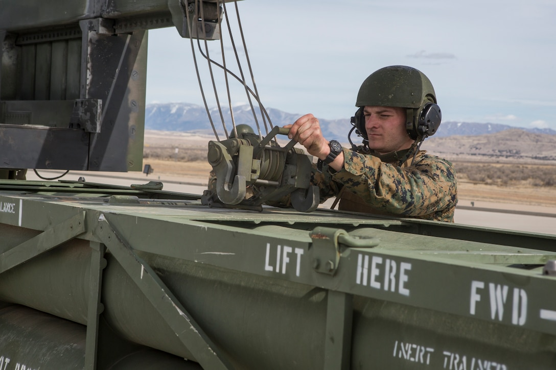 Marine Corps Sgt. Jeffery Hale, a launcher chief with Kilo Battery, 2nd Battalion, 14th Marine Regiment, hooks missile pods to a hoist on an M142 High Mobility Artillery Rocket System (HIMARS) at Dugway Proving Grounds, Utah, March 30, 2018. Marines from Kilo Battery flew from Fort Campbell, Ky., to Dugway where they offloaded and fired four HIMARS missiles, demonstrating a unique capability that will give commanders more options to deal with threats when other options are not appropriate.