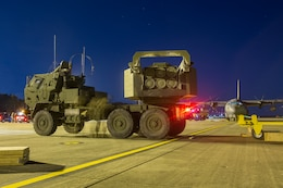 Marines from Kilo Battery, 2nd Battalion, 14th Marine Regiment, inspect a M142 High Mobility Artillery Rocket System (HIMARS) after being offloaded from an Air Force MC-130, on Fort Campbell, Ky., March 30, 2018. Marines from Kilo Battery flew from Fort Campbell to Dugway Proving Grounds, Utah, where they offloaded and fired four HIMARS missiles, demonstrating a unique capability that will give commanders more options to deal with threats when other options are not appropriate.