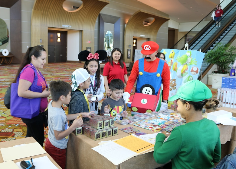 The family of Senior Airman Faustino Estrada, 445th Logistics Readiness Squadron, registers at a Mario themed table during the Yellow Ribbon Reintegration Program held in Orlando, Florida March 16, 2018