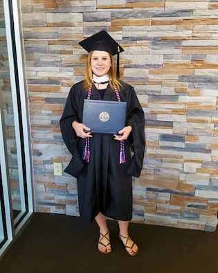 2nd Lt. Sam Norville posing with her college diploma after graduating.