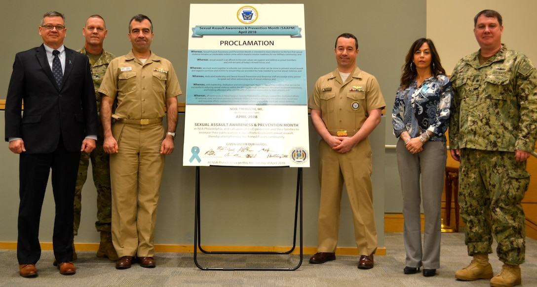 NSA Philadelphia tenant command representatives and Sexual Assault Prevention and Response program leads stand together after signing the 2018 Sexual Assault Awareness and Prevention Month proclamation at DLA Troop Support in Philadelphia April 3.