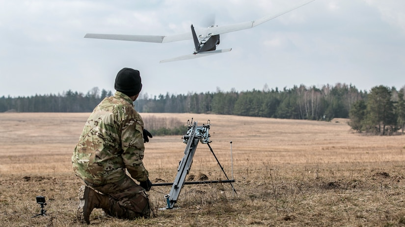 Kneeling soldier watches a drone in flight.