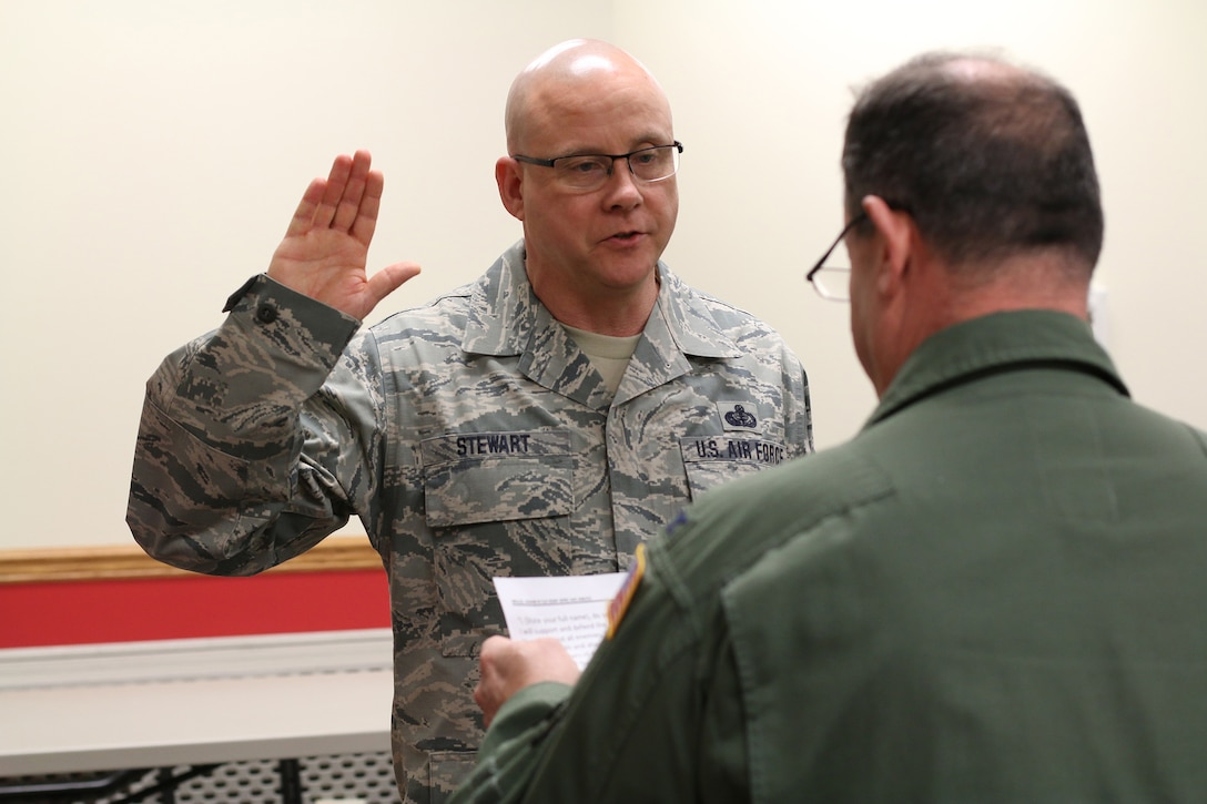 Col. Adam Willis, 445th Airlift Wing commander, administers the Oath of Enlistment to Chief Master Sgt. Paul Stewart, 445 AW command chief, March 3, 2018. This event marks Chief's Stewart's final enlistment.