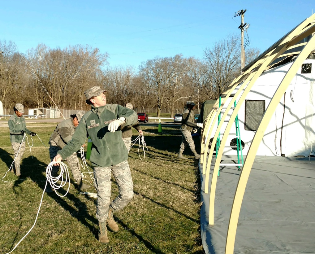 Staff Sgt. Taylor Anliker, 445th Force Support Squadron, tosses tent securing ropes as part of the assembly of a temporary lodging facility constructed during the March 4, 2018 unit training assembly at Wright-Patterson Air Force Base, Ohio.