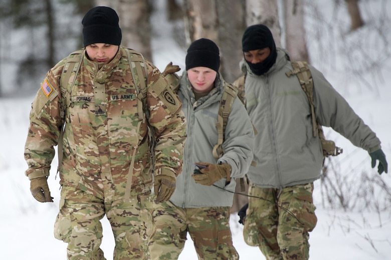 Army Sgt. Carlos Porras, a native of Burlington, NC, assigned to Hawk Company, 3rd Battalion, 509th Parachute Infantry Regiment, 4th Infantry Brigade Combat Team (Airborne), 25th Infantry Division, U.S. Army Alaska, leads Soldiers over an icy berm during a land navigation course on Joint Base Elmendorf-Richardson, Alaska, April 4, 2018.  The Soldiers used their skills to plot courses using a lensatic compass, protractor, and a 1:25,000 scale map to navigate to, and locate points using provided grid coordinates within a predetermined time.
