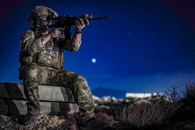 An airman sits on a ledge and aims a rifle against a deep blue, moonlit sky.