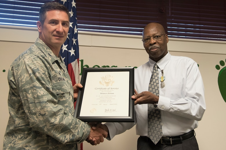 Col. John Chastain, left, 23d Maintenance Group (MXG) commander and Arlonzo Nelson, 23d MXG computer assistant, pose for a photo, during a retirement ceremony March 29, 2018, at Moody Air Force Base, Ga. Nelson is retiring after 30 years of civilian service here. (U.S. Air Force photo by Airman Eugene Oliver)