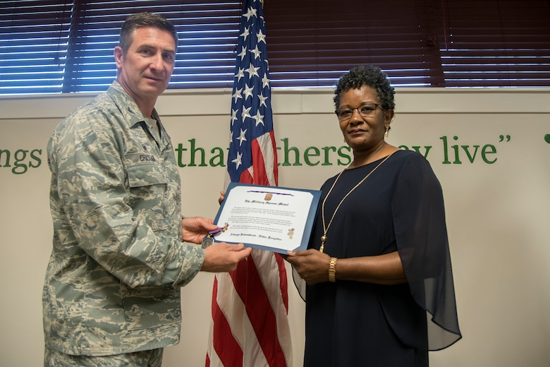 Col. John Chastain, left, 23d Maintenance Group (MXG) commander, and Cynthia Nelson, spouse of Arlonzo Nelson, 23d Maintenance Group computer assistant, pose for a photo, during a retirement ceremony, March 29, 2018, at Moody Air Force Base, Ga. Nelson is retiring after 30 years of civilian service here. (U.S. Air Force photo by Airman Eugene Oliver)
