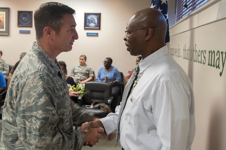 Col. John Chastain, left, 23d Maintenance Group (MXG) commander, shakes hands with Arlonzo Nelson, 23d MXG computer assistant during a retirement ceremony, March 29, 2018, at Moody Air Force Base, Ga. Nelson is retiring after 30 years of civilian service here. (U.S. Air Force photo by Airman Eugene Oliver)