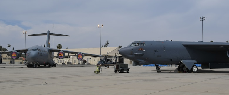A B-52 Stratofrtress, assigned to the 307th Bomb Wing, Barksdale Air Force Base, Louisiana, sits next to a C-17 Globemaster III, assigned to the 452nd Air Refueling Wing, at March Air Reserve Base, California, April 5, 2018.
