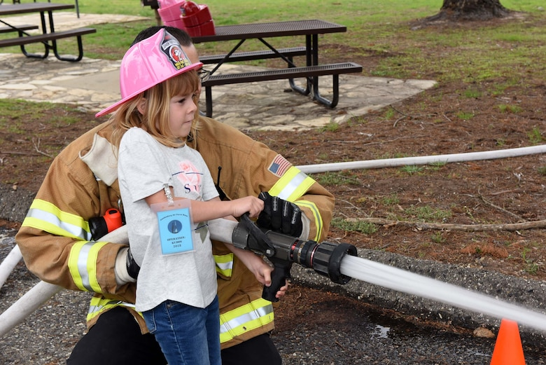 A military child uses a firefighter hose during Kids Understanding Deployment Operations, April 4, 2018, Vandenberg Air Force Base, Calif. KUDOS is a program developed to give children a deeper understanding of the military deployment process and equipment utilized during a deployment. (U.S. Air Force photo by Tech. Sgt. Jim Araos/Released)