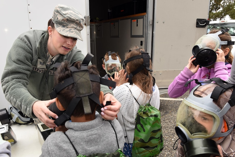 Staff Sgt. Ashley Lexvold, 30th Civil Engineer Squadron plans and operations, fits military children with protective masks during Kids Understanding Deployment Operations, April 4, 2018, Vandenberg Air Force Base, Calif. KUDOS is a program developed to give children a deeper understanding of the military deployment process and equipment utilized during a deployment. (U.S. Air Force photo by Tech. Sgt. Jim Araos/Released)