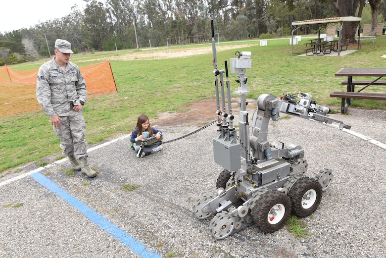 Senior Airman Tyler Erwin, 30th Civil Engineer Squadron explosive ordnance disposal specialist, assists a military child with an EOD robot during Kids Understanding Deployment Operations, April 4, 2018, Vandenberg Air Force Base, Calif. KUDOS is a program developed to give children a deeper understanding of the military deployment process and equipment utilized during a deployment. (U.S. Air Force photo by Tech. Sgt. Jim Araos/Released)