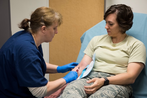 2nd Lt. Tera Hammond, 374th Medical Group clinical nurse and simulated patient, is prepped for an IV during helicopter patient transport training, March 30, 2018, at Yokota Air Base, Japan.
