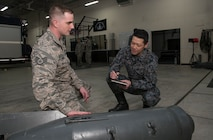 U.S. Air Force Staff Sgt. Kyle Miller, left, the 35th Civil Engineer Squadron explosive ordnance disposal NCO in charge, explains the makeup of a Russian bomb to Japan Air Self-Defense Force Master Sgt. Tomomune Segawa, a Tohoku EOD School instructor, at Misawa Air Base, Japan, March 29, 2018. Tohoku instructors attended the course in order to better their ordnance disposal skills for future bilateral missions. Once complete, the instructors took their newly gained knowledge and delivered it to their units. (U.S. Air Force photo by Senior Airman Sadie Colbert)