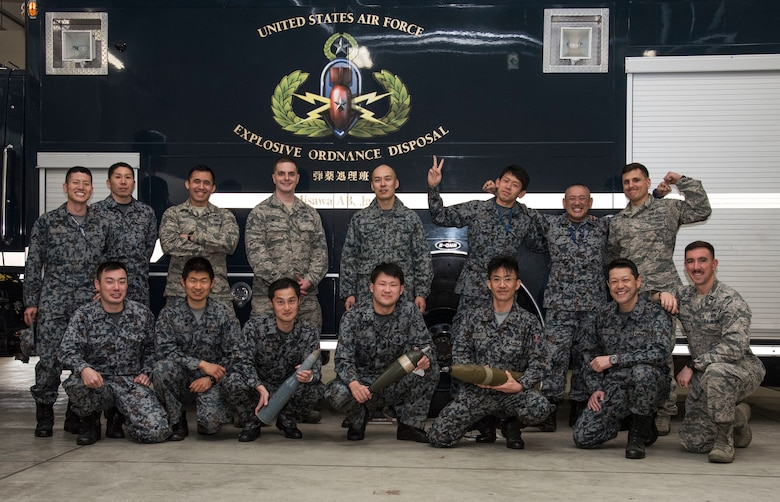 Airmen with the Japan Air Self-Defense Force 3rd Air Wing weapons maintenance technicians, Tohoku Sub Base, Tohoku, Japan,explosive ordnance disposal instructors, and the 35th Civil Engineer Squadron EOD team pose for a group photo at Misawa Air Base, Japan, March 29, 2018. For two days U.S. Air Force EOD technicians educated JASDF personnel of the basics on unexploded ordnances by going through classroom lectures to share how to classify different UXOs, practice searching for detonated ordnances and how to properly dispose of them. The teams worked hand-in- hand with each other, fortifying their bilateral teamwork and increasing the swiftness of their techniques. (U.S. Air Force photo by Senior Airman Sadie Colbert)