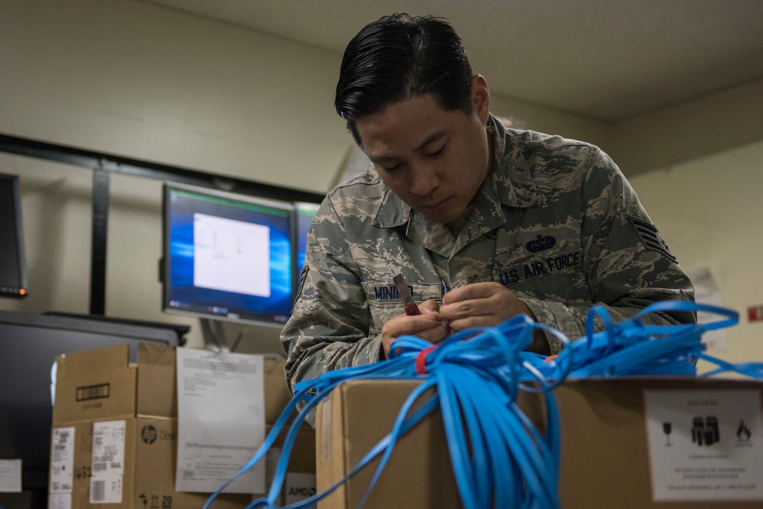 Staff Sgt. Justin Raymond Minimo, 374th Communications Squadron Operations Flight client systems technician craftsman, prepares an Ethernet cable for a clip at Yokota Air Base, Japan, April 4, 2018.