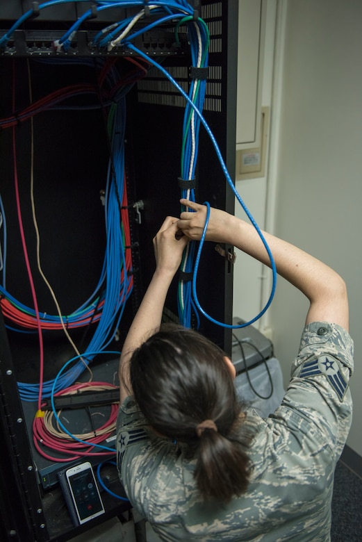 Senior Airman Amy Kristoffersen, 374th Communications Squadron Operations Flight client systems technician journeyman, performs some cable management prior to completing a printer swap at Yokota Air Base, Japan, April 4, 2018.
