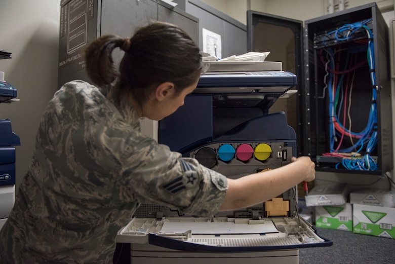 Senior Airman Amy Kristoffersen, 374th Communications Squadron Operations Flight client systems technician journeyman, opens up the side of a printer prior to performing a printer swap at Yokota Air Base, Japan, April 4, 2018.