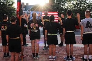 Students stand with their backs to the camera as they take part in a ceremony to join the ROTC.