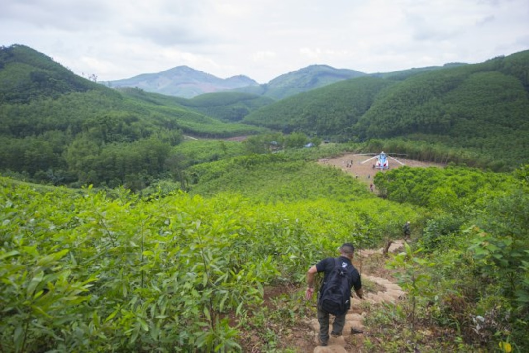 A member of the Defense POW/MIA Accounting Agency hikes a trail down from an excavation site March 17, 2018, in Quang Ngai province, Vietnam, where an American pilot crashed during the Vietnam War. A joint recovery team climbed 700 feet in elevation along a half-mile trail every day to the site as part of the mission. (U.S. Army photo by Sean Kimmons)