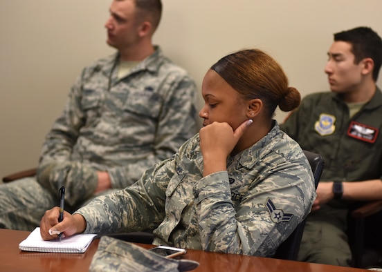 A female in uniform sits at a table taking notes.