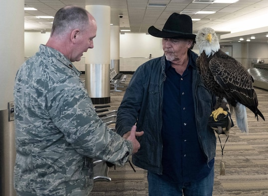 Maj. Pat McDonald, 934th Communications Squadron commander, greets Al Louis Cecere, Founder and President of the American Eagle Foundation, and Challenger the Eagle at the Minneapolis-St. Paul International Airport April 4.  Challenger will fly during the national anthem at the Minnesota Twins opening day April 5. (Air Force Photo/Paul Zadach)