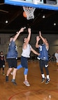 John Bone, a forward on the 20th Intelligence Squadron basketball team and a major with the 55th Wing Judge Advocate office, makes a layup while two defenders from the 595th Aircraft Maintenance Squadron try and stop him during the 2018 Offutt Intramural Basketball championship at the Offutt Field House April 5. Bone led all scorers with 25 in the title game. (U.S. Air Force photo by Charles Haymond)