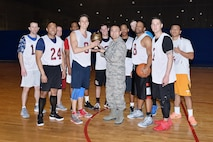 U.S. Air Force Lt. Col. Sean Park, 55th Mission Support Group deputy commander, presents the 2018 Offutt Intramural Basketball championship trophy to the 20th Intelligence Squadron after they defeated the 595th Aircraft Maintenance Squadron 75-67 at the Offutt Field House April 5. The 20th completes their season at 14-3, while the 595th finishes at 12-3. (U.S. AIr Force photo by Charles Haymond)