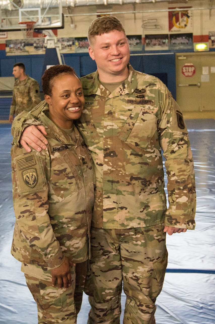 Retired Army Sgt. Franz Walkup poses for a photo with Pennsylvania Army National Guard Sgt. Maj. Stephanie Armstrong, following an Operation Proper Exit town hall meeting at Camp Arifjan, Kuwait.