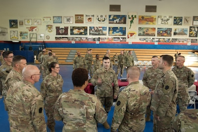 Retired Army Spc. Justin Lane, center, speaks to 28th Infantry Division soldiers at Camp Arifjan, Kuwait,