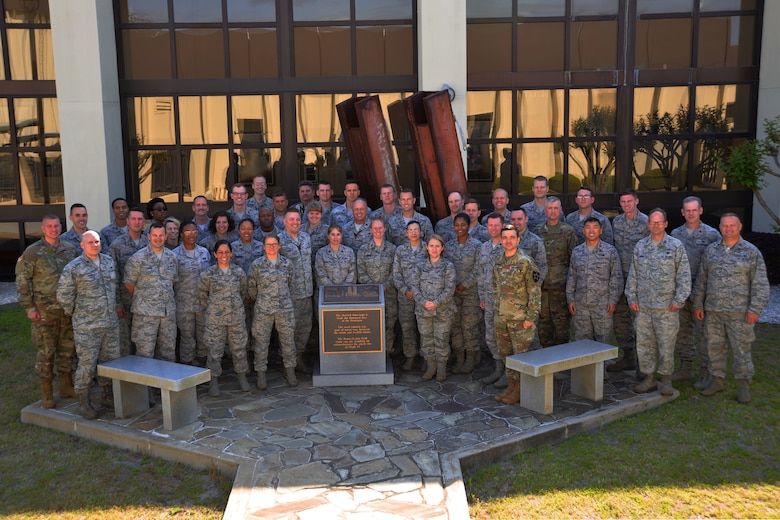 Military staff judge advocates and enlisted legal staff members pause for a photo in front of the 9/11 Memorial during their visit to the 601st Air Operations Center March 27. (Air National Guard photo by Maj. Andrew Scott)