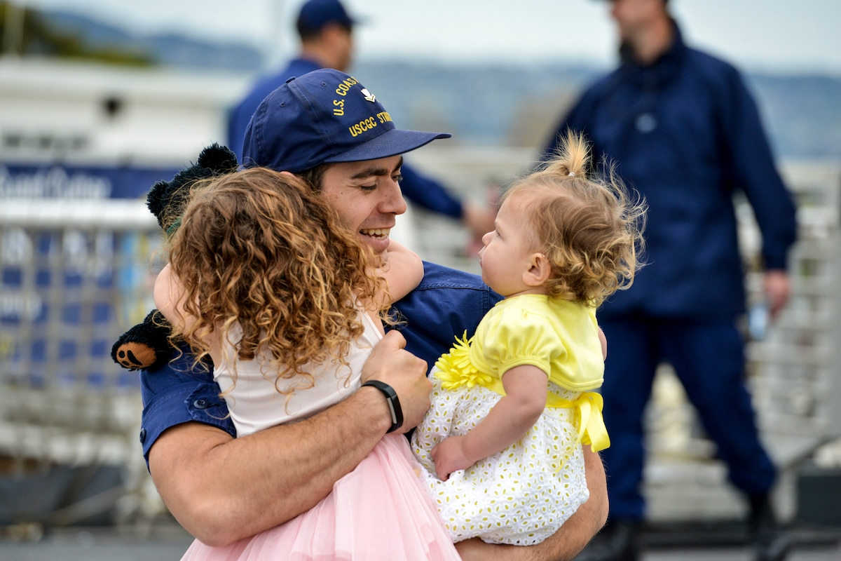 A Coast Guardsman embraces two little girls, one of whom holds a teddy bear, on a pier.
