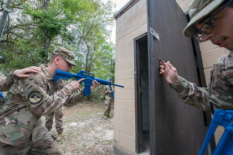 Airmen 1st Class David Medeiros, 824th Base Defense Squadron fireteam member, left, prepares to enter a building during dismounted operations training, March 27, 2018, at Moody Air Force Base, Ga. The dismounted ops training is part of an Initial Qualification Training, which gives new Airmen coming into the 820th Base Defense Group an opportunity to learn a baseline of basic combat skills that will be needed to successfully operate within a cohesive unit while in a deployed environment. (U.S. Air Force photo by Airman Eugene Oliver)