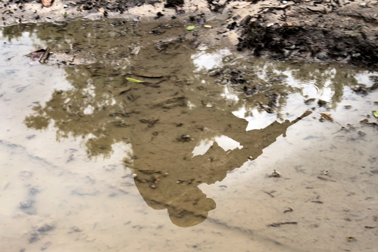 A puddle shows the reflection of an Airman from the 820th Base Defense Group (BDG) during a dismounted operations training, March 27, 2018, at Moody Air Force Base, Ga. The dismounted ops training is part of an Initial Qualification Training, which gives new Airmen coming into the BDG an opportunity to learn a baseline of basic combat skills that will be needed to successfully operate within a cohesive unit while in a deployed environment. (U.S. Air Force photo by Airman Eugene Oliver)
