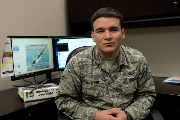A young man sits in a chair while wearing the Airman Battle Uniform with two computer monitors behind him.