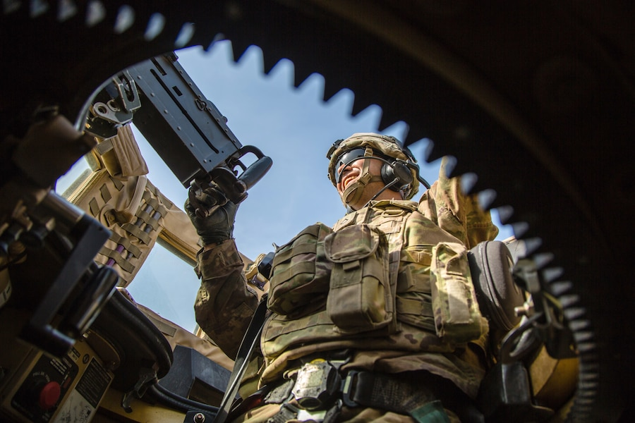 A soldier stands in a military vehicle and looks outwards.