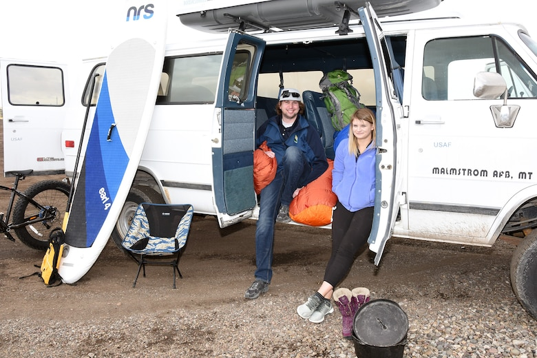 180404-F-UQ541-0819 Drew Schlieder and Michaela Klein, 341st Force Support Squadron Outdoor Recreation Center staff, pose with an adventure Air Force van at Pow Wow Park April 4, 2018, at Malmstrom Air Force Base, Mont. Malmstrom's Outdoor Recreation Center rents seasonal sports gear and transportation equipment for people to get out and experience the Mountain States. (U.S. Air Force photo by Kiersten McCutchan)