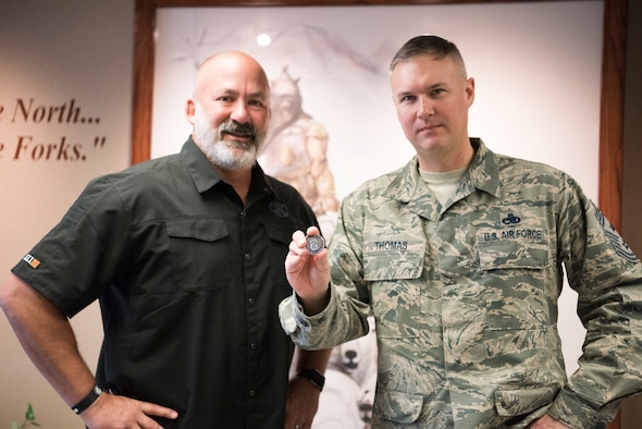 Chief Master Sgt. Brian Thomas, 319th Air Base Wing command chief (right), presents his chief coin alongside mentor and friend, (ret.) Chief Master Sgt. Calvin Markham, March 23, 2018, at Grand Forks Air Force Base, N.D. Markham gifted Thomas this coin when Thomas pinned on chief in 2013. (U.S. Air Force photo by Airman 1st Class Elijaih Tiggs)