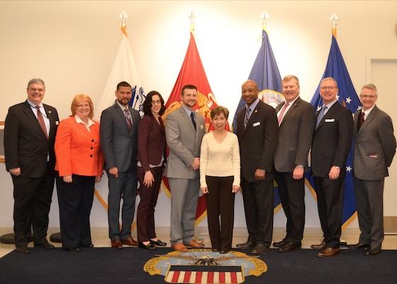 The Defense Acquisition University Senior Service College Fellowship Program participants pose with Hue Nguyen, center, DLA Troop Support flag room supervisor, at DLA Troop Support in Philadelphia April 3, 2018.