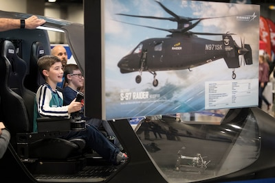 Jack Boren, left, and his brother Grant, pilot a helicopter simulator during the USA Science and Engineering Festival in Washington.