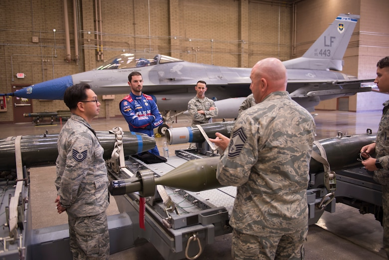 Alexander Rossi, Andretti Autosport racecar driver, listens as Chief Master Sgt. Daniel Gregory, 56th Maintenance Group superintendent, and other members of the 56th MXG, talk about aircraft weapons and ordnance at Luke Air Force Base, Ariz., April 5, 2018. Rossi's visit raised awareness of the manpower and resources that go into driving the mission at an Air Force base. (U.S. Air Force photo by Senior Airman Ridge Shan)
