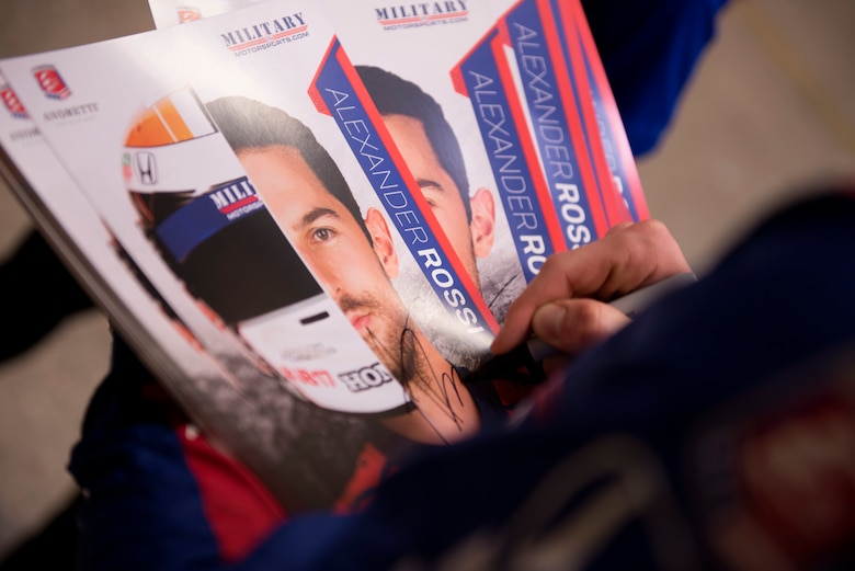 Alexander Rossi, Andretti Autosport racecar driver, autographs photos of himself to hand out to Airmen at Luke Air Force Base, Ariz., April 5, 2018. Rossi visited the base as part of a small delegation from Andretti Autosport in order to learn more and the mission and Airmen here. (U.S. Air Force photo by Senior Airman Ridge Shan)