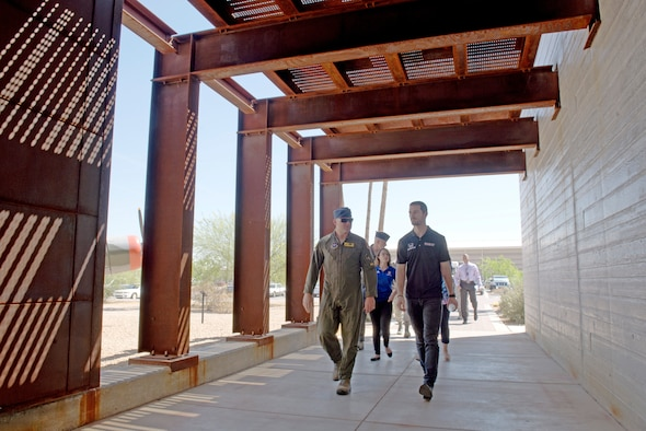 Lt. Col. Rhett Hierlmeier, 61st Fighter Squadron commander; and Alexander Rossi, Andretti Autosport racecar driver, walk through the entrance to the 61st FS operations building at Luke Air Force Base, Ariz., April 5, 2018. Rossi and other delegates from Andretti Autosport learned about the lives and work of pilots, maintainers and other Airmen who support the mission to build the future of airpower. (U.S. Air Force photo by Senior Airman Ridge Shan)