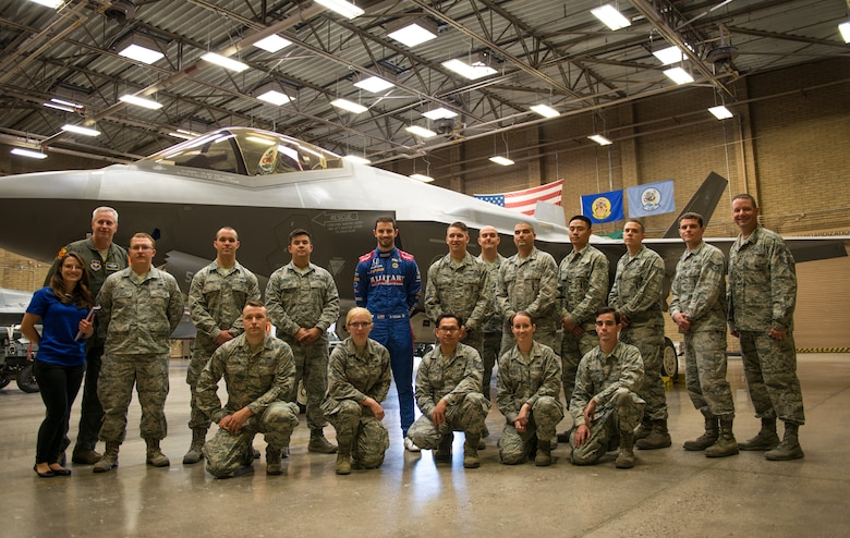 Alexander Rossi, Andretti Autosport team race car driver, poses for a group photo with Thunderbolts from the 61st Aircraft Maintenance Unit at Luke Air Force Base, Ariz., April 5, 2018. During their visit, Rossi and his team visited various units around base to gain insight on the mission of Luke and its Airmen. (U.S. Air Force photo by Airman 1st Class Alexander Cook)