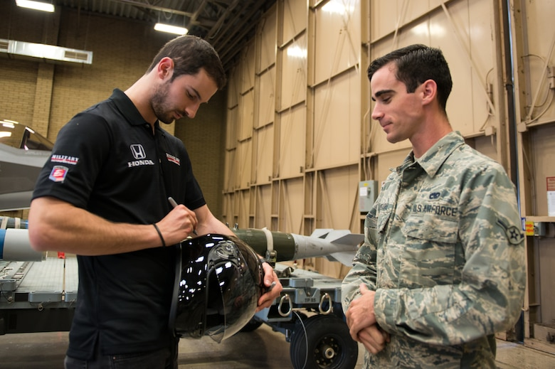 Alexander Rossi, Andretti Autosport team race car driver, autographs a helmet during his visit to Luke Air Force Base, Ariz., April 5, 2018. The Andretti Autosport team visited various units around base to gain insight on the mission of Luke and its Airmen. (U.S. Air Force photo by Airman 1st Class Alexander Cook)