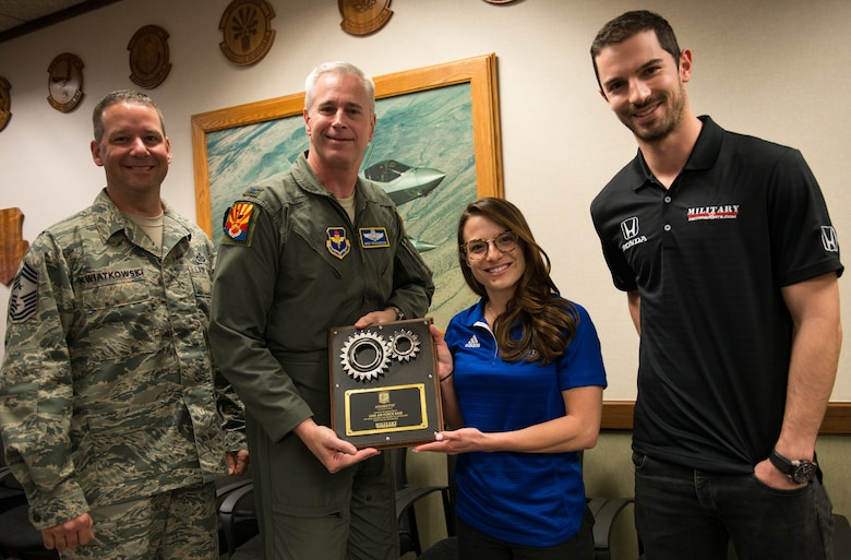 Col. Michael Richardson, 56th Fighter Wing vice commander, receives a gift of appreciation from the Andretti Autosport team at Luke Air Force Base, Ariz., April 5, 2018. The visit provided the Andretti Autosport team insight on the mission of Luke and its Airmen. (U.S. Air Force photo by Airman 1st Class Alexander Cook)