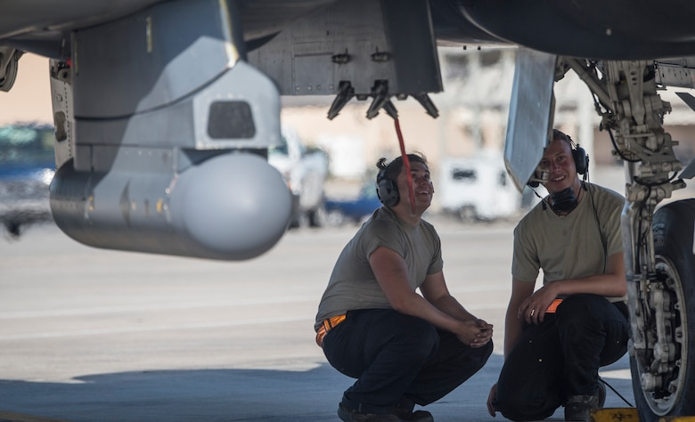 Image of Airman Matthew Ozuzun and Airman 1st Class Leopoldo Jauregoz, 391st Aircraft Maintenance Unit crewchiefs, await the take off of their F-15E Strike Eagle at Tyndall Air Force Base, Florida, April 3, 2018. Combat Archer and Hammer provided the opportunity to evaluate the squadron's ability to perform in a tempo more comparable to a deployed environment. (U.S. Air Force photo by Staff Sgt Jeremy L. Mosier)